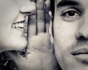 une personne susurre à l'oreille d'une autre