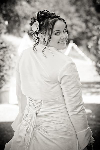 La mariée de dos regarde l'objectif par dessus son épaule