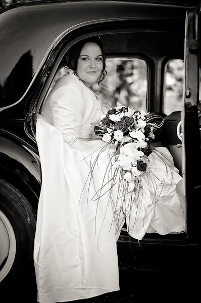 La mariée assise à l'arrière de la traction avec son bouquet