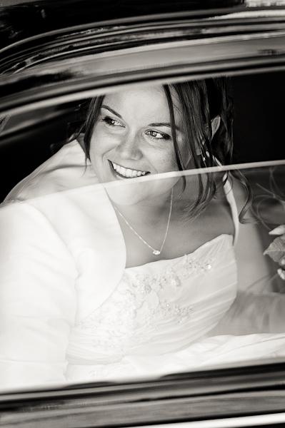 portrait de la mariée à travers la vitre de la voiture