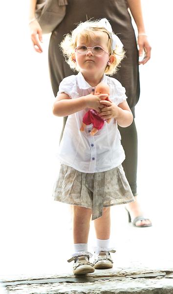 Portrait d'une petite fille et sa poupée entrant dans l'église en high key