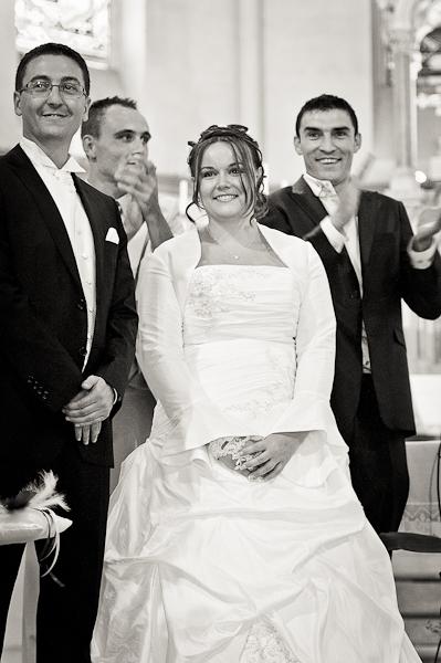 Les mariés à l'église avec les témoins qui applaudissent