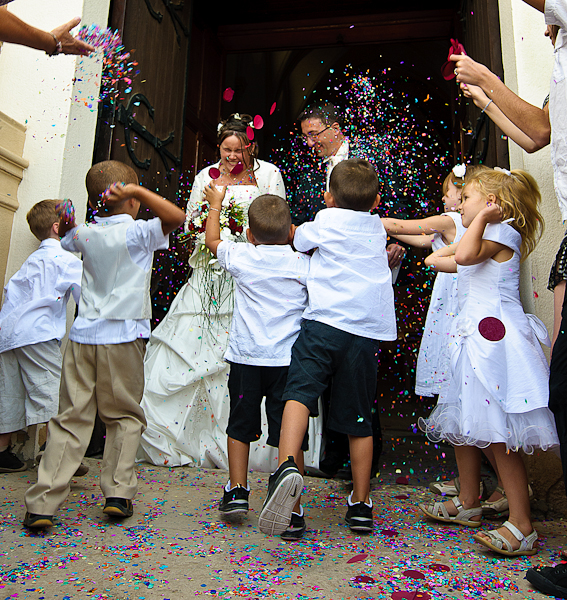 un groupe d'enfants jettent des confettis au couple de mariés