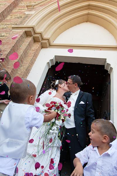 le couple de marié s'embrasse à la sortie de l'église sous une pluie de confettis