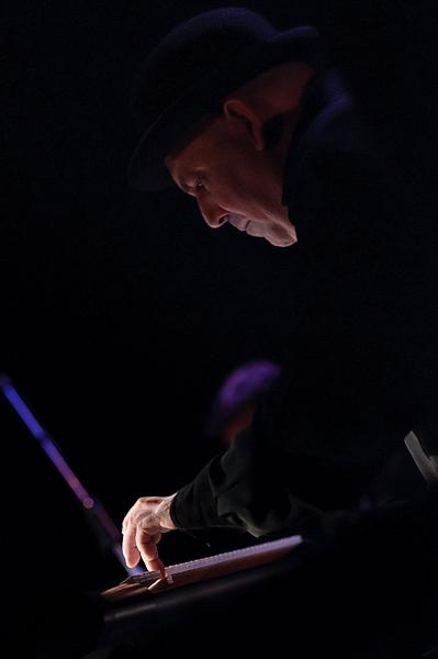 pianiste jouant sur ses claviers de profile avec un léger éclairage latérale