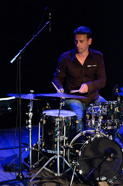 batteur jouant sur sa batterie sur scène avec spots bleus