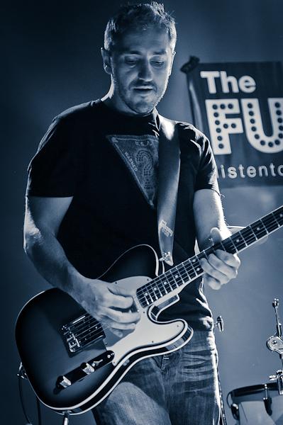Le guitariste en train de jouer devant la banderole du groupe