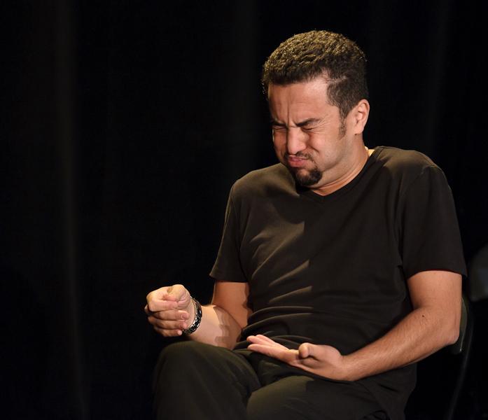 Le comédien est assis sur une chaise et mime un psy en train d'éternuer