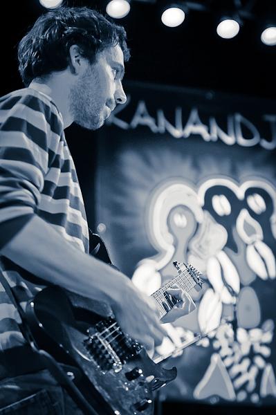 Le guitariste du groupe Kanandjo avec l'affiche en fond