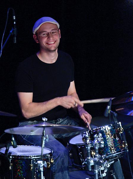 Le batteur jouant derrière sa batterie avec un grand sourire