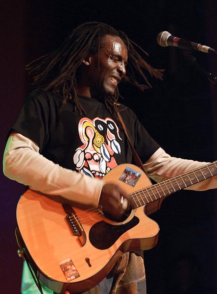 Le chanteur secoue la tête en jouant de la guitare