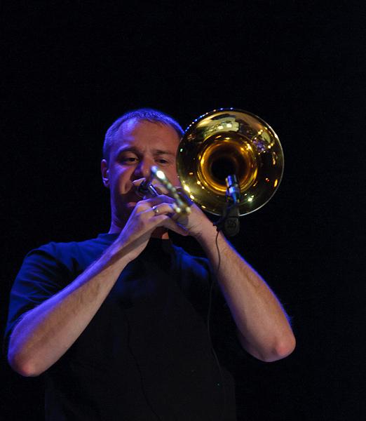 Le tromboniste en plein solo sous une lumière bleue
