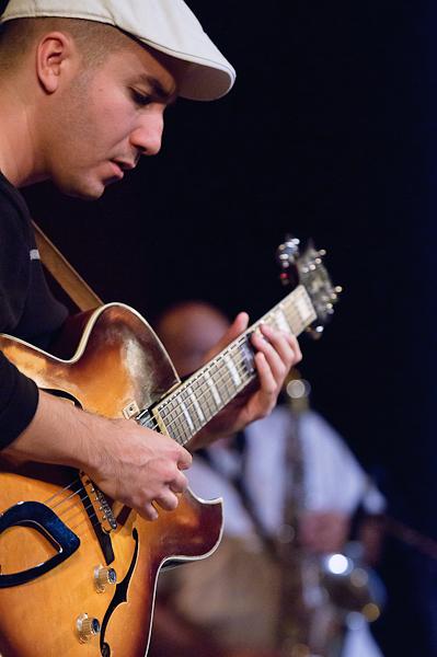 le guitariste de profil jouant de sa guitare