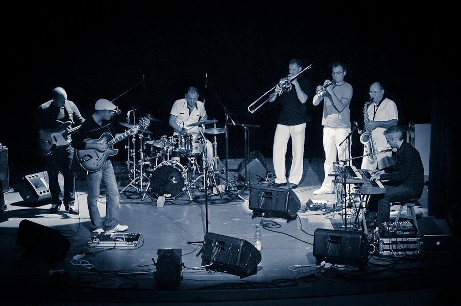 la scène entière avec le guitariste et le bassiste à gauche, le batteur au centre et la section cuivre et le clavier à droite