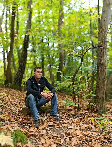 portrait d'un jeune homme assis sur une bûche en forêt en bokeh panorama