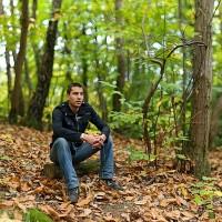 portrait d'un jeune homme assis sur une bûche en forêt avec la méthode brenizer