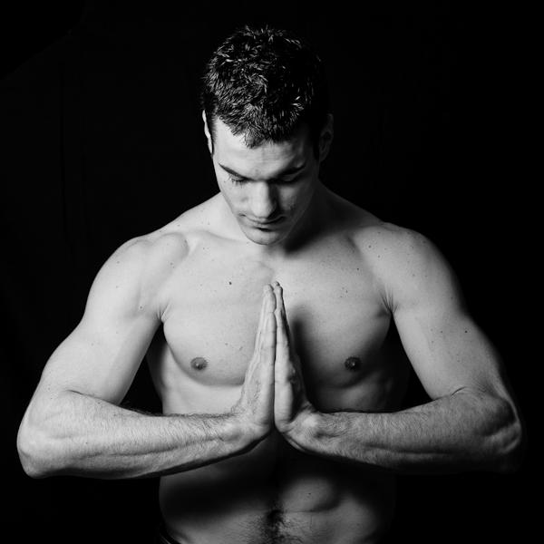 portrait d'un homme musclé avec les mains jointes en pleine méditation