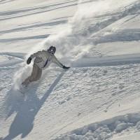 Un snowboardeur ridant dans la poudreuse en plein virage