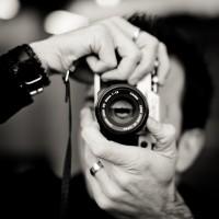 Gros plan sur un homme utilisant un appareil photo argentique avec un 50mm
