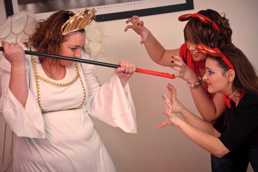 Un ange se defend avec une fourche contre l'attaque de deux démons furieux