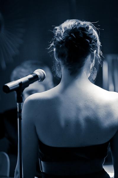 La chanteuse de dos à côté de son micro en noir et blanc virage bleu