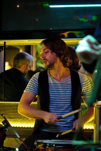 Le batteur en pleine concentration et le guitariste de dos dans le reflet du miroir