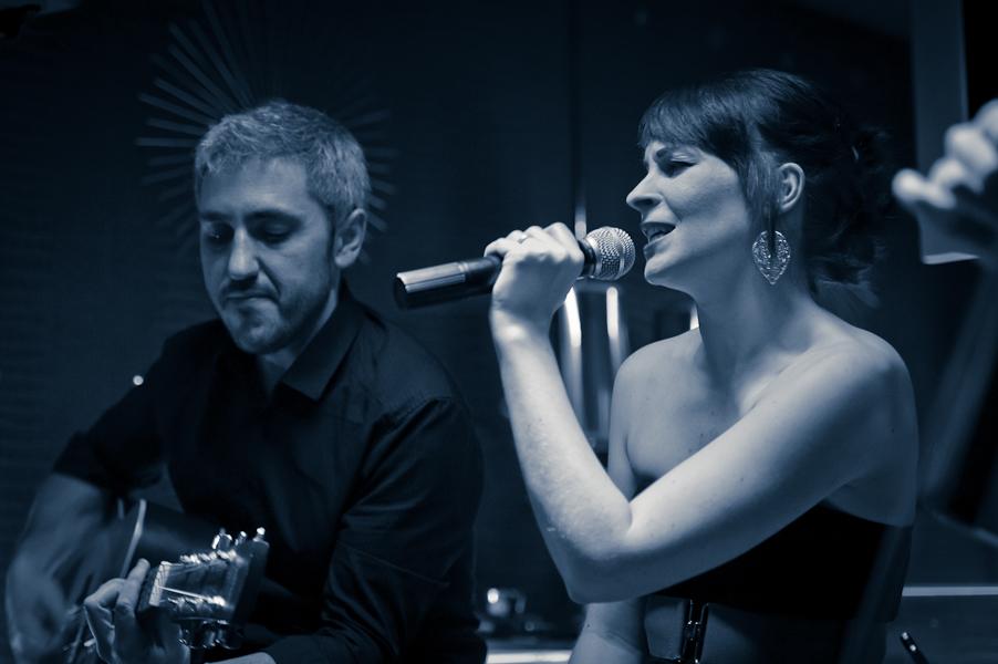 La chanteuse et le guitariste côte à côté en noir et blanc virage bleu
