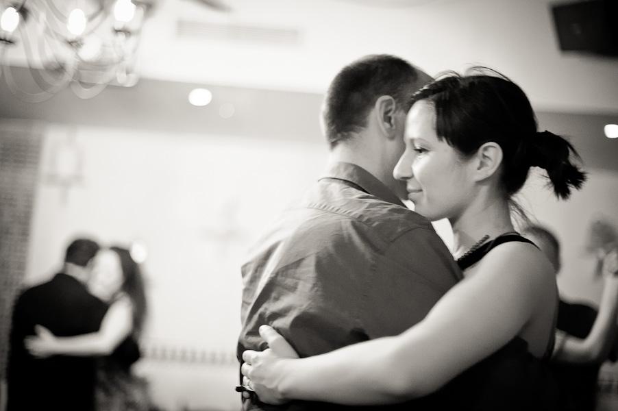 un couple danse tendrement en premier plan et un deuxième couple danse en arrière plan