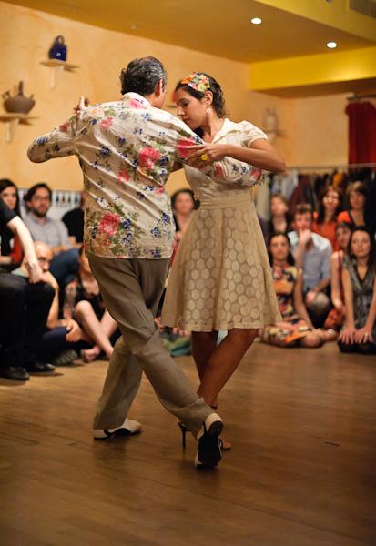Un danseur et une danseuse font une démonstration de tango au centre du public