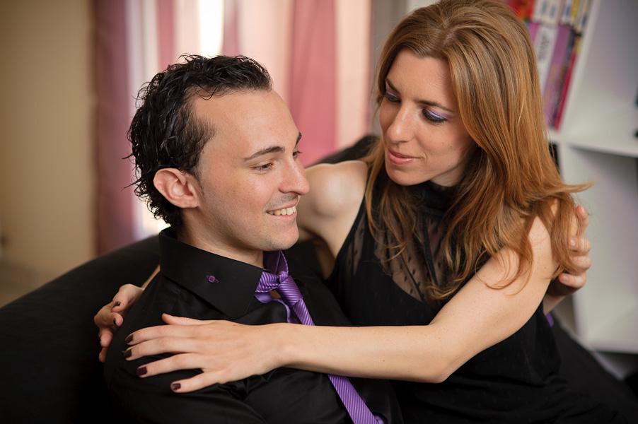 Un bel homme est assis sur un canapé dans les bras de sa ravissante femme