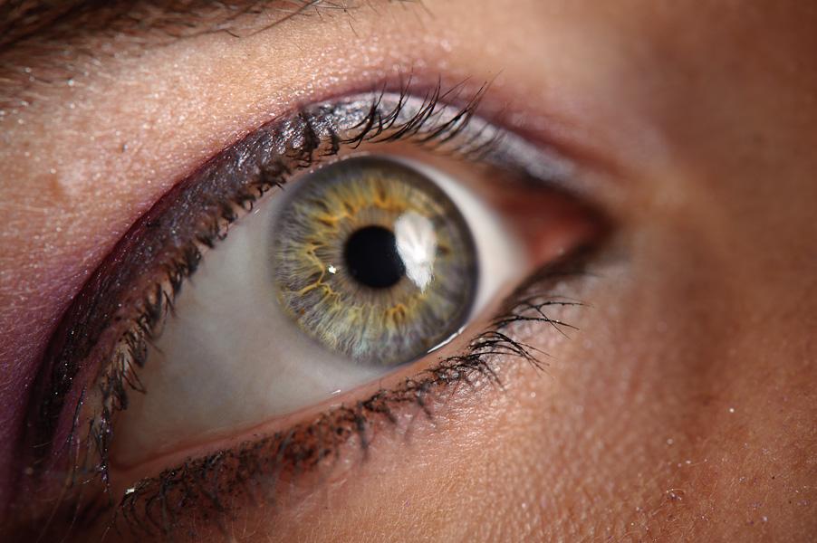 Gros plan sur de beaux yeux verts maquillé de violet