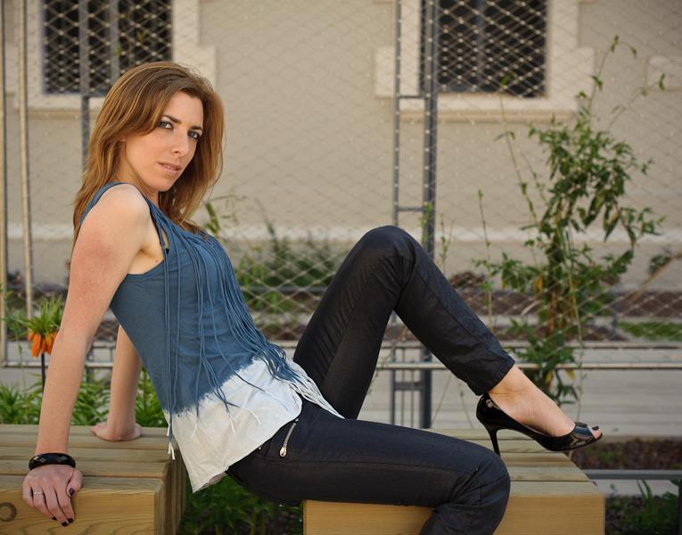 Portrait en extérieur d'une belle femme rousse assise sur un banc public