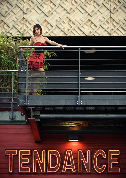 """Portrait d'une jeune femme en robe rouge au dessus d'un néon rouge inscrivant """"tendance"""""""