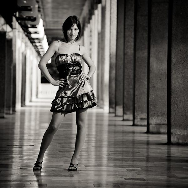 Portrait d'une modèle brune en robe au milieu d'une allée en noir et blanc