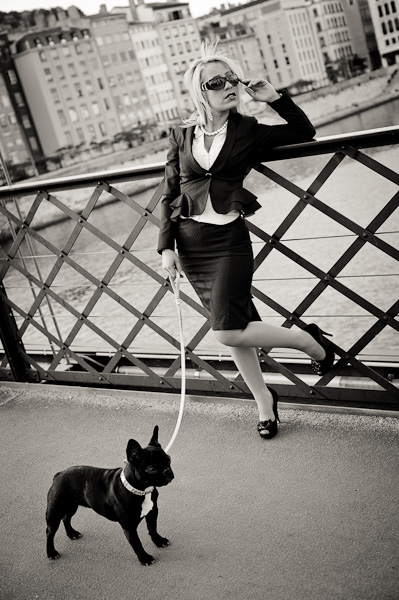 Portrait d'une jeune femme chic et son bulldog français sur un pont