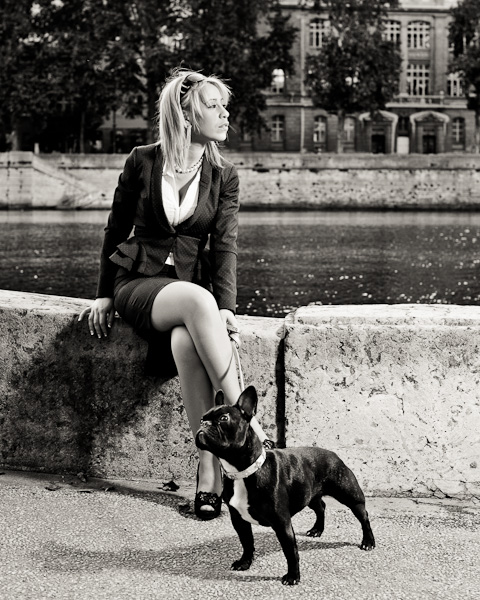 Portrait d'une femme blonde en tailleur avec son bulldog français au bord de l'eau