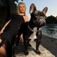 Une jeune femme chic et son bulldog français au bord de l'eau