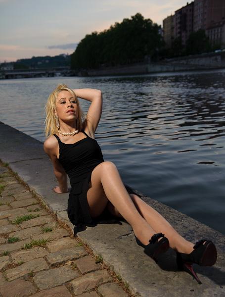 Portrait d'une modèle blonde alongée au bord d'une rivière