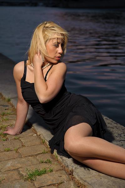 Photo studio mode en extérieur d'une modèle blonde en robe noire alongé sur les pavés près de l'eau