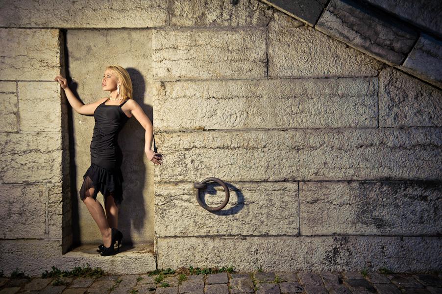 Une jeune femme blonde pose de profil contre un mur en pierre sur un quai