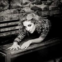 Portrait d'une jeune femme blonde frisée allongée sur un banc
