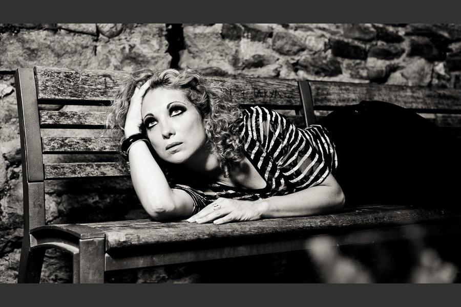 Portrait d'une modèle blonde allongée sur un banc publique