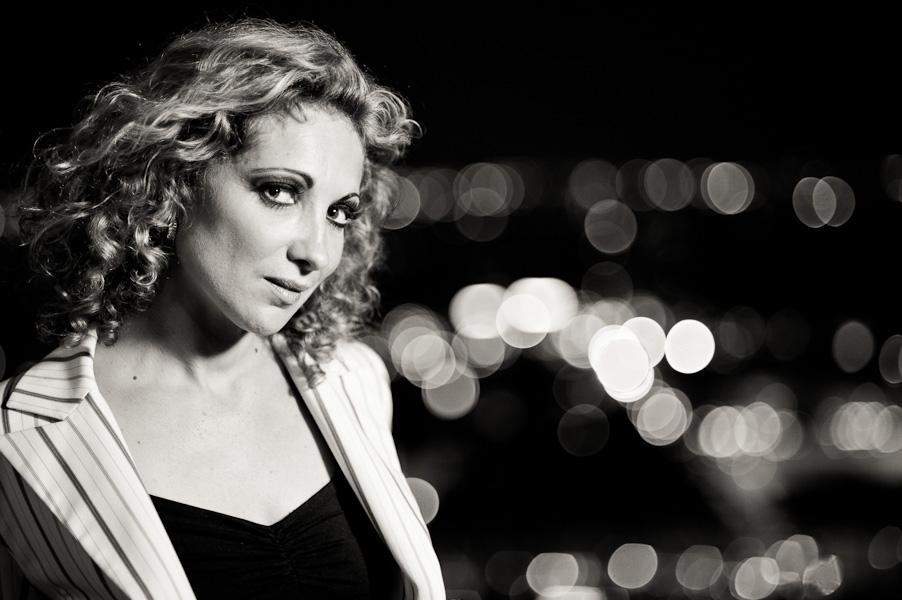 Portrait d'une belle femme blonde dos à la ville illuminée