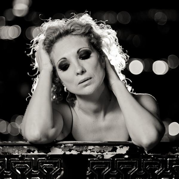 Portrait d'une jeune femme accoudée sur un portail en fer la nuit