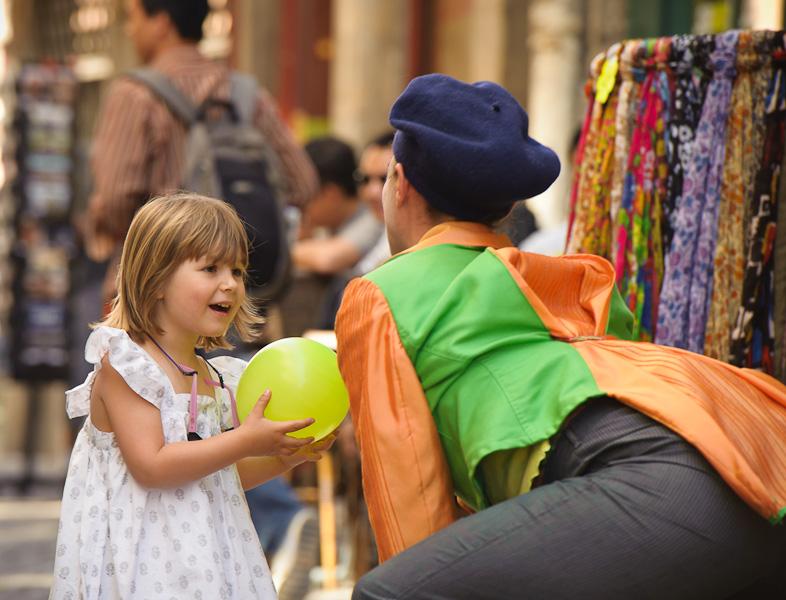 Une clown offre un ballon à une petite fille