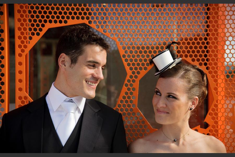 Portrait serré d'un couple de jeunes mariés devant une grille alvéolée orange