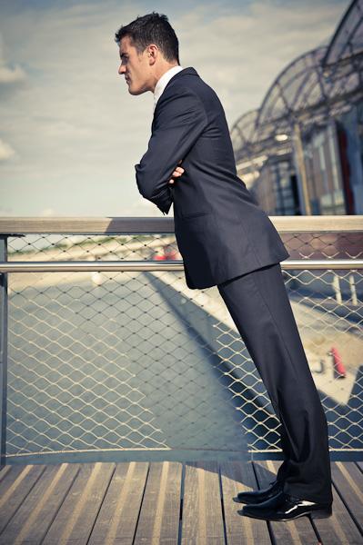 Un jeune homme tient debout penché à 45 degré sur une passerelle