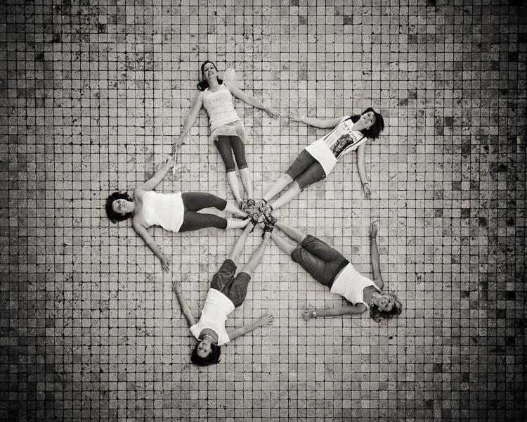 Cinq jeunes femmes sont allongées sur le sol et se tiennent la main pour former une étoile