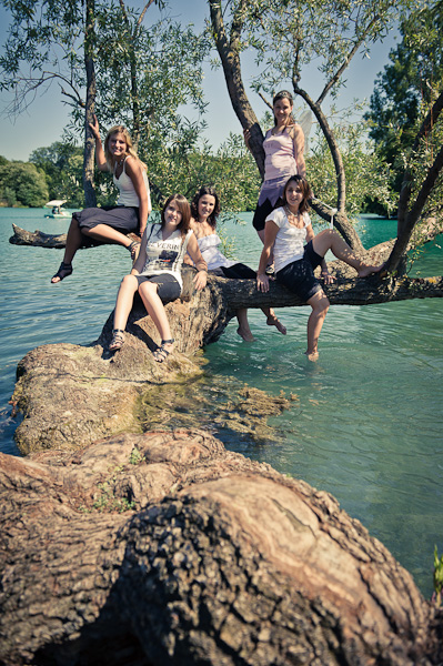 Portraits de cinq copines assises sur un tronc d'arbre au bord d'un lac
