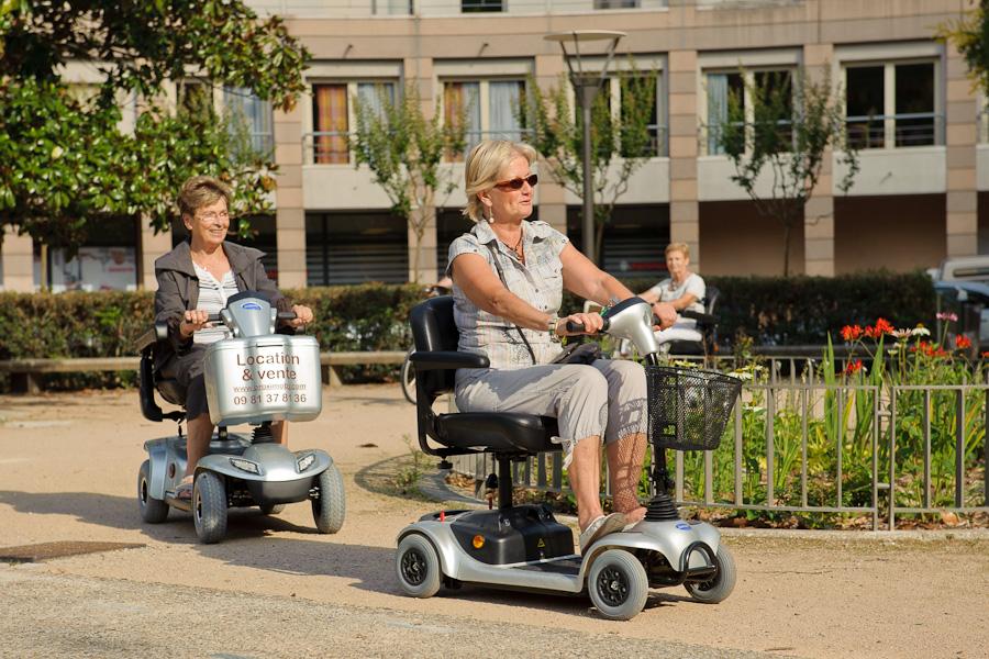 Un groupe de jeunes retraités se déplace en scooter électrique dans un petit parc